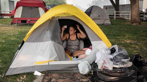 Stacey Kahny fixes her hair inside her tent at the evacuation center at the Jackson County Fairgrounds in Central Point, Oregon, on September 16. Kahny lived with her parents at a trailer park in Phoenix, Oregon, that was destroyed by fire.