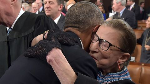"""President Barack Obama hugs Ginsburg as he arrives to deliver the State of the Union address in January 2015. Ginsburg didn't shy away from fashion. <a href=""""https://www.cnn.com/2018/03/21/politics/ruth-bader-ginsburg-scrunchies/index.html"""" target=""""_blank"""">She often accessorized</a> her black robe with intricate lace collars and an array of different gloves."""