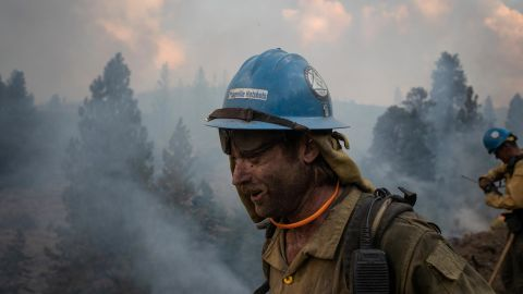 Firefighter Kirk McDusky walks past smoke rising from the Brattain Fire in Paisley, Oregon, on September 18.