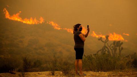 A woman takes photos as the Bobcat Fire burns in Juniper Hills, California, on September 18.