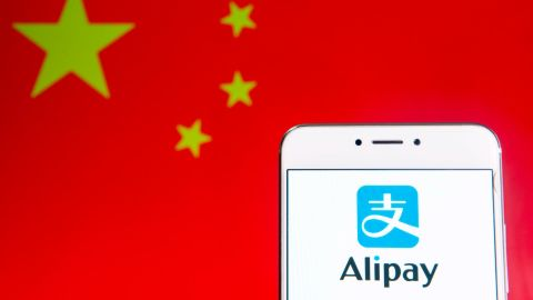 HONG KONG - 2019/04/06: In this photo illustration a Chinese online payment platform owned by Alibaba Group, Alipay, logo is seen on an Android mobile device with People's Republic of China flag in the background. (Photo Illustration by Budrul Chukrut/SOPA Images/LightRocket via Getty Images)