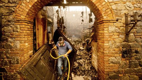 Cellar worker Jose Juan Perez extinguishes hotspots at Castello di Amorosa, a Calistoga winery that was damaged in the Glass Fire.