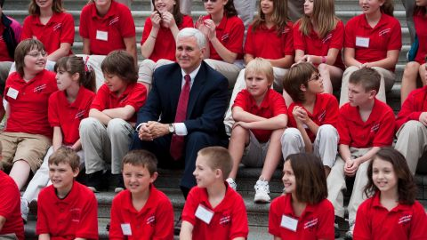 Pence sits with the Royerton Elementary School choir as it prepares to sing patriotic songs on the House steps in May 2011.