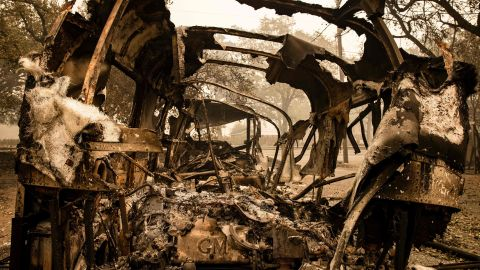 Vehicles burned in the Glass Fire sit outside of a home that survived in Calistoga on September 30.