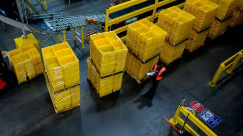 A man works at a distrubiton station at the 855,000-square-foot Amazon fulfillment center in Staten Island, one of the five boroughs of New York City, on February 5, 2019. - Inside a huge warehouse on Staten Island thousands of robots are busy distributing thousands of items sold by the giant of online sales, Amazon. (Photo by Johannes EISELE / AFP)        (Photo credit should read JOHANNES EISELE/AFP via Getty Images)