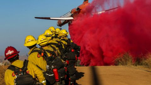 An airplane drops fire retardant on the Bruder Fire in Redlands, California, on October 15.