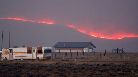Flames rise from mountain ridges near a farmstead as a wildfire burns near Granby, Colorado, on Thursday, October 22.