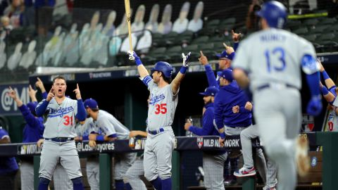 Joc Pederson and Cody Bellinger of the Los Angeles Dodgers react to a Max Muncy solo home run in the fifth inning during Game 5 of the World Series at Globe Life Field on Sunday, October 25, in Arlington, Texas.