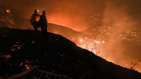Firefighters look out over a burning hillside as they fight the Blue Ridge Fire in Yorba Linda, California, on Monday, October 26.