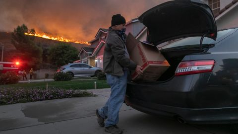 A man evacuates his home as flames from the Blue Ridge Fire approach in Chino Hills, California, on Tuesday, October 27.