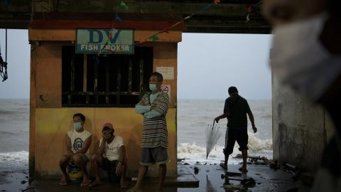 People monitor the sea level and waves as typhoon Goni makes landfall on Sunday in Atimonan, Philippines.