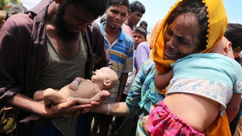 """Rohingya refugees fleeing Myanmar hold their infant son Abdul Masood, <a href=""""http://www.cnn.com/2017/09/14/asia/myanmar-rohingya-muslim-family-mourns-infant-son/index.html"""" target=""""_blank"""">who died when their boat capsized</a> before reaching Bangladesh on September 13."""