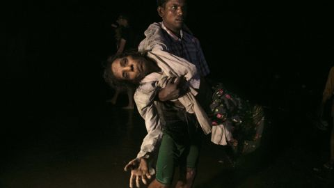 Sona Banu is carried ashore on September 27 by Nobi Hossain after crossing the Naf River by boat from Myanmar to near Cox's Bazar, Bangladesh.
