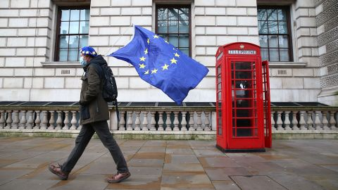 """A man wearing an EU flag-themed beret and carrying an EU flag is seen on Whitehall in central London on December 11, 2020. - Prime Minister Boris Johnson on December 10 vowed to go the """"extra mile"""" for a Brexit trade deal but instructed his government to prepare for Britain to crash out of the European Union's single market at the end of this year. (Photo by Hollie Adams/AFP/Getty Images)"""