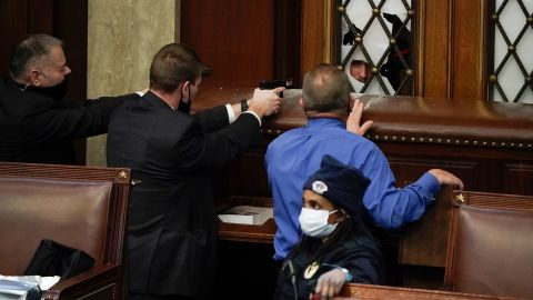 Law enforcement officers point their guns at a door that was vandalized in the House chamber after the Capitol was breached.