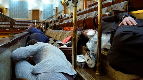 People take shelter in the House chamber as rioters try to break in. House members were given gas masks that were under the seats, according to a pool reporter on the House floor.