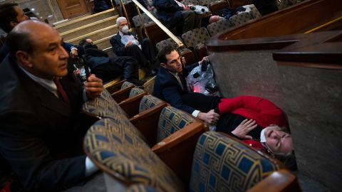 US Rep. Jason Crow, a Democrat from Colorado, comforts US Rep. Susan Wild, a Democrat from Pennsylvania, while taking cover in the House chamber.