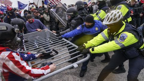 Trump supporters try to break through a police barrier.