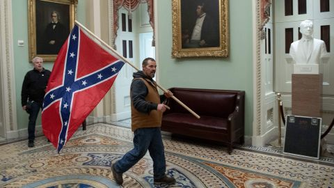 """A Trump supporter <a href=""""https://www.cnn.com/2021/01/07/us/capitol-confederate-flag-fort-stevens/index.html"""" target=""""_blank"""">carries a Confederate battle flag</a> in the Capitol Rotunda. During the Civil War, the closest any insurgent carrying a Confederate flag ever came to the Capitol was about 6 miles, during the Battle of Fort Stevens in 1864."""