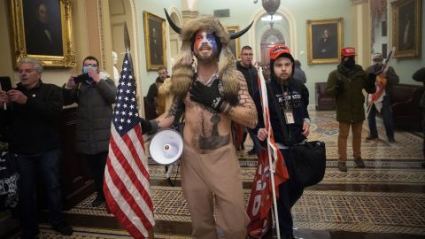 """One of <a href=""""https://www.cnn.com/2021/01/07/us/insurrection-capitol-extremist-groups-invs/index.html"""" target=""""_blank"""">the most recognizable figures in the crowd</a> was a man in his 30s with a painted face, fur hat and a helmet with horns. The protester, Jake Angeli — known by followers as the QAnon Shaman — quickly became a symbol of the bizarre and frightening spectacle. In recent months, Angeli has been a regular presence at pro-Trump protests in Arizona, including demonstrations outside the Maricopa County vote-counting center."""
