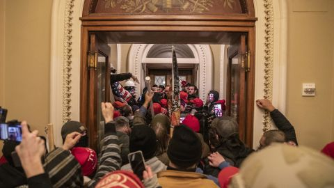 Rioters walk through the Capitol after breaching barricades to the building.