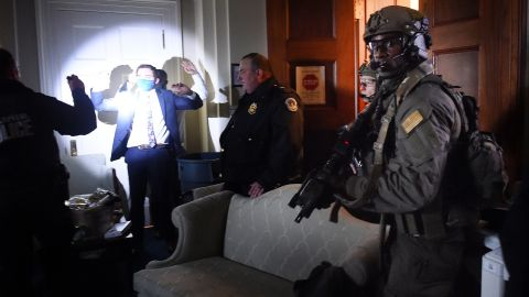 Congressional staffers hold up their hands while Capitol Police SWAT teams secure the US Capitol.