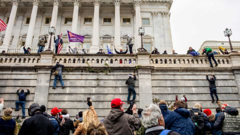 Trump supporters climb a wall outside the Capitol.