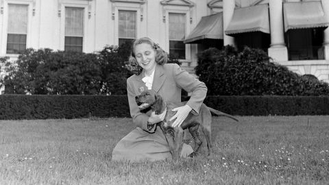 Harry Truman's daughter, Margaret, holds their Irish setter, Mike, outside the White House in 1945.