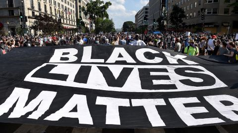 """Protesters deploy a """"Black Lives Matter"""" banner near the White House during a demonstration against racism and police brutality, in Washington, DC, on June 6, 2020."""