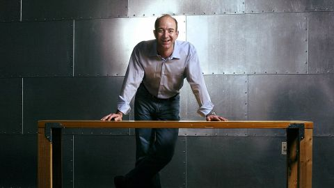 Jeff Bezos stands with one of Amazon's trademark door-desks at the company's Seattle headquarters in 2004.