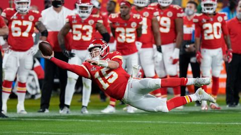 Mahomes attempts a pass while falling down in the second half.