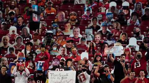 Fans celebrate among cardboard cutouts in the stands.