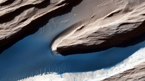 Although Mars isn't geologically active like Earth, surface features have been heavily shaped by wind. Wind-carved features such as these, called yardangs, are common on the Red Planet. On the sand, the wind forms ripples and small dunes. In Mars' thin atmosphere, light is not scattered much, so the shadows cast by the yardangs are sharp and dark.