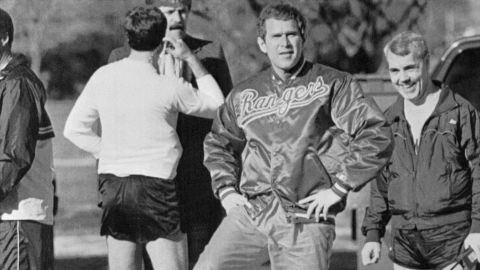 """Bush has a """"leg up"""" on his father as he clowns around for the camera in 1990. A year earlier, the younger Bush became part-owner of the Texas Rangers baseball team."""
