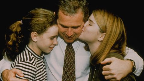 Bush hugs his daughters Barbara, left, and Jenna after his election win in 1994.
