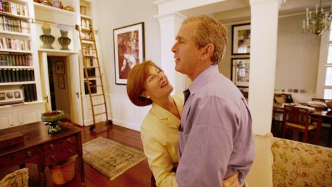 Bush is embraced by his wife, Laura, at the governor's mansion in November 2000. Bush lost the popular vote but edged Gore in the Electoral College. His victory didn't become official until December, when the US Supreme Court, by a 5-4 margin, suspended a recount in the deciding state of Florida. Gore conceded the next day.