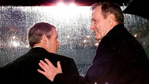 Bush gets a pat on the back from his dad during his inauguration ceremonies.