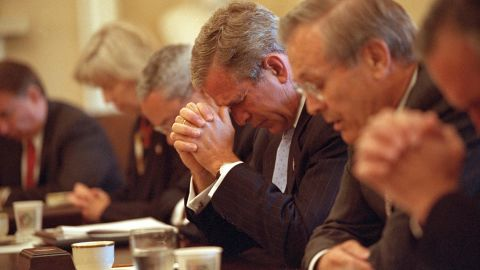Bush and his Cabinet bow their heads in prayer before a White House meeting on September 14, 2001.