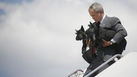 Bush walks off Air Force One carrying the family dogs Barney and Miss Beazley in 2006.