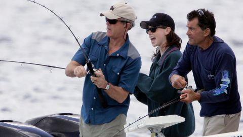 Bush reels in a catch in Kennebunkport, Maine, in 2007. Watching is his daughter, Barbara, and cousin Billy.