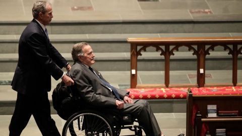 Bush pushes his father's wheelchair at the funeral service for his mother, Barbara, in April 2018.