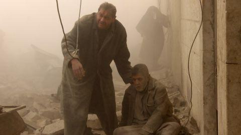 An injured man is helped following an airstrike in Aleppo's Maadi neighborhood on December 17, 2013.