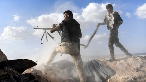 A member of the Syrian pro-regime forces fires a machine gun as a comrade holds his feeding ammunition belt on November 11, 2017. It was during an advance toward rebel-held positions west of Aleppo.