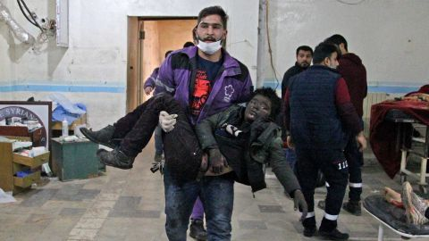 A member of the Syrian Violet Organization carries an injured boy at a makeshift hospital following a regime air strike on a vegetable market in Syria's last major opposition bastion of Idlib on January 15, 2020.