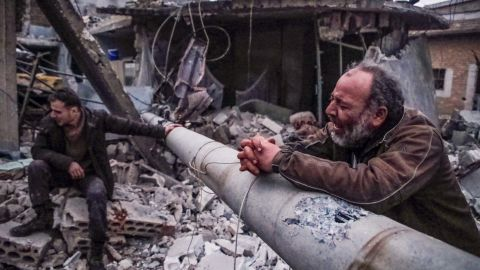 A Syrian man mourns the death of family members next to the rubble of his house following a reported airstrike on the village of Kafr Nuran, in the northern province of Aleppo, on January 21, 2020.