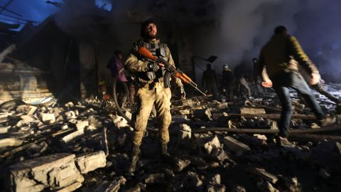 Members of Syrian Civil Defence and Turkish-backed Syrian forces search for victims in the aftermath of a car bomb explosion near a security checkpoint in the town of Azaz on March 19, 2020.