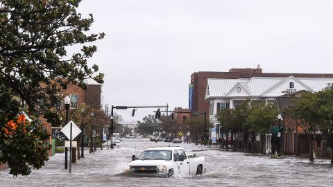 """TOPSHOT - A city worker drives through the flooded street during Hurricane Sally in downtown Pensacola, Florida on September 16, 2020. - Hurricane Sally barrelled into the US Gulf Coast early Wednesday, with forecasts of drenching rains that could provoke """"historic"""" and potentially deadly flash floods.The National Hurricane Center (NHC) said the Category 2 storm hit Gulf Shores, Alabama at about 4:45 am (0945 GMT), bringing maximum sustained winds of about 105 miles (165 kilometers) per hour.""""Historic life-threatening flooding likely along portions of the northern Gulf coast,"""" the Miami-based center had warned late Tuesday, adding the hurricane could dump up to 20 inches (50 centimeters) of rain in some areas. (Photo by CHANDAN KHANNA / AFP) (Photo by CHANDAN KHANNA/AFP via Getty Images)"""