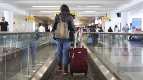 A traveler walks on a moving walkway in Terminal 4 at John F. Kennedy International Airport (JFK) in New York, U.S., on Friday, March 26, 2021. The TSA screened more than 1.3 million people both Friday and Sunday, setting a new high since the coronavirus outbreak devastated travel a year ago. Airlines say they believe the numbers are heading up, with more people booking flights for spring and summer, reports the Associated Press. Photographer: Angus Mordant/Bloomberg via Getty Images