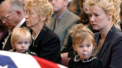 Renae Chapman holds her 2-year-old daughter, Amanda, during the funeral service for her husband, Army Sgt. 1st Class Nathan R. Chapman, in Fort Lewis, Washington, in January 2002. He was the first US soldier to be killed by enemy fire during the war in Afghanistan.