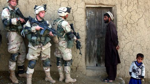 A man and his son watch US soldiers prepare to sweep their home in southeastern Afghanistan in November 2002.